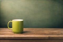 Green mug on wooden table