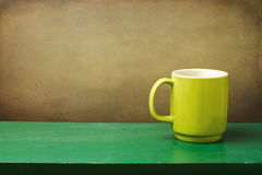 Green mug on wooden table Royalty Free Stock Photo