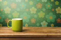 Green mug on wooden table. Over floral wallpaper Royalty Free Stock Photo