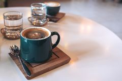 Green mugs of hot coffee and glasses of water on table in cafe. Closeup image of green mugs of hot coffee and glasses of water on table in cafe stock images