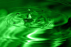 Green multi colored water drop bubbling Stock Images