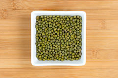 Green mung beans in white bowl on wood Royalty Free Stock Image