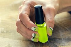 Kiwi art manicure. Green nail polish and skin care of a beauty female hands with green and white moon nail art manicure on a wooden background stock image