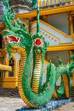Green naka statue in front of Thai Buddhist pagoda at Tiger Cave Royalty Free Stock Photo