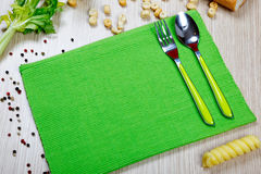 Green napkin with flatware. A green napkin with flatware on a table stock photo