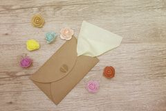 Green napkin sticks out of the craft envelope decorated with colorful flowers on wood. Flat lay studio image. stock photography