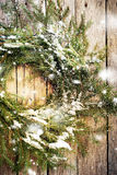 Green Natural Wreath with Snow on Wooden Background. Falling snow is drawn Royalty Free Stock Photo