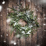Green Natural Wreath on Wooden Background with Falling Snow Stock Photos