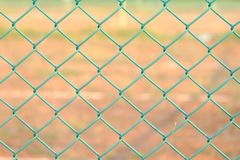 Green metal fence with sun light and blur yellow ground floor in outdoor space for background texture stock image