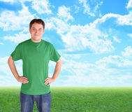 Green Nature Man Standing in Clouds and Grass. A man wearing a green t-shirt is smiling and standing in front of bright blue clouds and green nature grass. Use Royalty Free Stock Photo