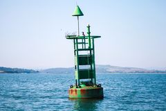 Green navigation buoy with cone topmark royalty free stock image