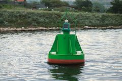 Green navigation buoy floating on sea water royalty free stock photography