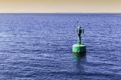 Green navigational buoy marker with solar panels Royalty Free Stock Image