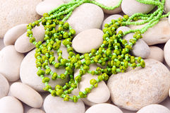 Green necklace against white stones Royalty Free Stock Image