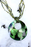 Green necklace in the snow Royalty Free Stock Images