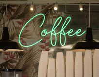 Green neon sign with text Coffee on wallpaper and boards behind stacked paper cups. Cursive green neon sign COFFEE in front of palm and flower wallpaper and wood royalty free stock photo