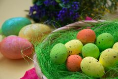 Green nest in a basket with small colorful Easter eggs, decoration, close-up easter concept, holiday tradition, blurred paints. Small colorful eggs in a nest royalty free stock photos
