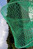 Green net for fish. Fish net yarn made of very durable. It is good for large fish, 1,2,5,7, kg. Post to fish on the boat. It shows the river, blue sky and forest stock image