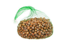 Green net with hazelnuts, isolated on white Royalty Free Stock Images