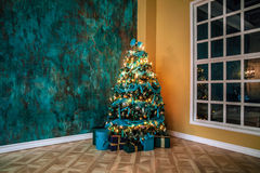 Green New Year tree decorated. With toys and balls. Christmas background with grunge plaster wall Stock Images