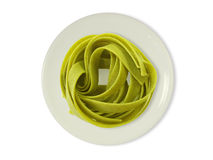 Green noodles on a plate. In front of a white background Stock Photos