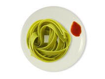 Green noodles on a plate with tomato sauce. In front of a white background Stock Photos