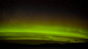 Green northern lights and myriad of stars Stock Photos