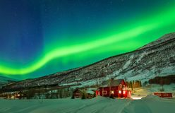 Green northern lights over rural county of northern Norway. Aurora Borealis over mountain and rural house in distant Northern Norway. Green light of aurora lay Stock Photography