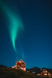 Green Northern Lights rising like smoke from red house at night in Greenland. This is a unique view of wispy green Aurora borealis that looked like it could have Stock Photos