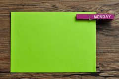A green note with a peg with the word monday. On a wooden background Royalty Free Stock Photo
