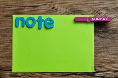 A green note with the word note and a peg with the word monday. On a wooden background Royalty Free Stock Photo