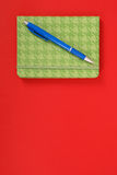 Green notebook and blue pen. Green closed notebook with blue pen isolated on red background with soft shadow, place for your text Stock Photography