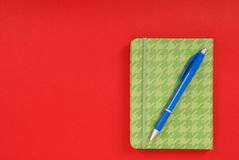 Green notebook and blue pen. Green notebook with blue pen isolated on red background with soft shadow, place for your text Royalty Free Stock Image