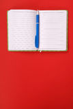 Green notebook and blue pen. Green notebook with blue pen isolated on red background with soft shadow, place for your text Stock Image