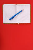 Green notebook and blue pen. Green notebook with blue pen isolated on red background with soft shadow, place for your text Stock Photo