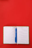 Green notebook and blue pen. Green notebook with blue pen isolated on red background with soft shadow, place for your text Royalty Free Stock Photos