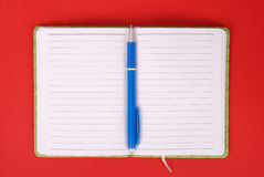 Green notebook and blue pen. Green open notebook with blue pen isolated on white background red soft shadow Clipping path Royalty Free Stock Photo