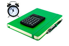 Green notebook, calculator and alarm clock Royalty Free Stock Photo