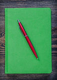Green notepad ball-point pen on vintage wood board office concep Royalty Free Stock Photos