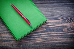 Green notepad ballpoint pen on vintage wood board education conc Stock Images