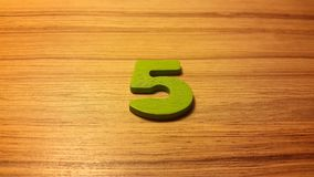 Green number 5 on wooden background Stock Images