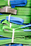 Green nylon soft lifting slings stacked in piles. Warehouse of finished products for industrial enterprises Royalty Free Stock Photos