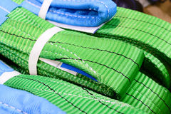 Green nylon soft lifting slings stacked in piles. Stock Photography