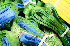 Green nylon soft lifting slings stacked in piles. Warehouse of finished products for industrial enterprises Stock Images