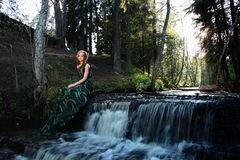 Green nymph look woman near waterfall in the forest Stock Photography