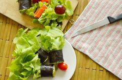Green oak and sausage wrapped by seaweed cooking on chop block Stock Images