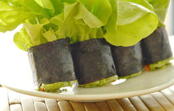 Green oak and sausage wrapped by seaweed on dish Stock Photo