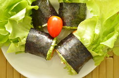 Green oak and sausage wrapped by seaweed on plate Stock Photography