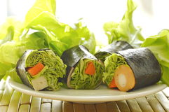 Green oak and sausage wrapped by seaweed on plate Royalty Free Stock Photos