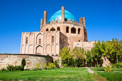 Green oasis with trees and historical 14 century blue domed mausoleum. Dome of Soltaniyeh near Zanjan city, Iran. UNESCO World Heritage Site, so called Iranian Stock Photo